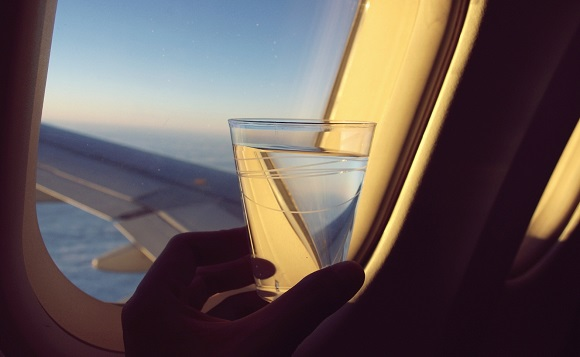 In flight beverage looking out of plane window